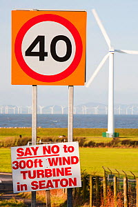 Protest sign about a new wind turbine in Seaton near Workington, Cumbria, UK, with onshore wind turbines and the offshore Robin Rigg wind farm visible. January 2012 - Ashley Cooper