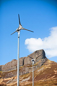 Wind turbines beneath An Sgurr, Isle of Eigg. Isle of Eigg produces all the energy the island needs from renewable energy. Eigg, Scotland, UK, May. - Ashley Cooper