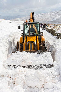 JCB clearing a way through massive snow drifts blocking the Kirkstone Pass road above Ambleside,Lake District, UK. March 2013 - Ashley Cooper