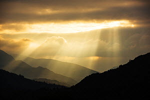 Shafts of light at dusk over Wrynose pass and the Coniston hills from Ambleside, Lake District, England, UK. September 2015 - Ashley Cooper