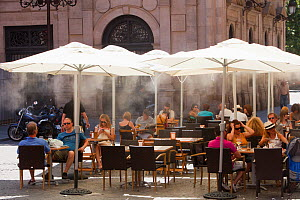 Cafe is using mist sprayers to try to cool customers down during hot weather, Seville, Andalucia, Spain, May 2011  -  Ashley Cooper