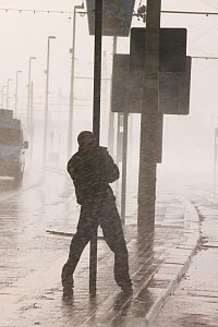 Man holding onto post during severe storm with hurricane force winds, Blackpool, England, UK, November 2007. - Ashley Cooper