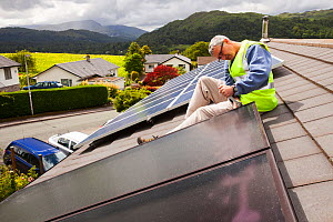 Workman fitting solar thermal panels for heating water, to a house roof, Ambleside, Cumbria, UK,. June 2012 - Ashley Cooper