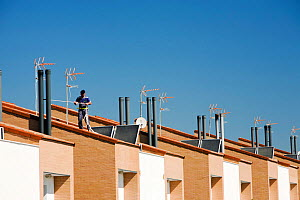 Man working on solar water heaters on a house roof in Sanlucar La Mayor in Andalucia, Spain. May 2011 - Ashley Cooper