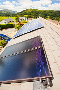 Solar thermal panels for heating hot water with solar PV electric panels behind on a house roof in Ambleside, Lake District, UK. July 2012 - Ashley Cooper