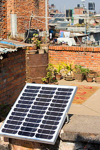 A tiny solar photo voltaic panel on a rooftop in Kathmandu, big enough to power a couple of lights in the house below, Nepal. January 2013  -  Ashley Cooper