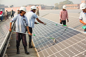 Workers washing dust off solar panels at station run by Tata power on the roof of an electricity company in Delhi, India, to make them more efficient. December 2013 - Ashley Cooper
