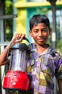 Boy holding a solar lantern, charged from the solar panelsfrom WWF project to supply renewable electricity to a remote island in the Sunderbans, Ganges, India. December 2013 - Ashley Cooper