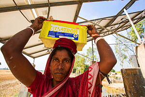 Woman collecting solar charged batteries from  WWF project to supply electricity to a remote island in the Sunderbans, Ganges Delta, India. December 2013 - Ashley Cooper