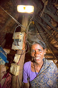 Dalit woman / untouchable woman in her hut, illuminated by an electric light, powered by an A4 sized solar panel, that charges a battery, and enables her to have light. Karnataka, India. December 2013  -  Ashley Cooper