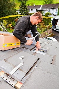 A techinician fitting roof brackets to a house roof in Ambleside, Cumbria, UK, to support solar photo voltaic panels. August 2011 - Ashley Cooper