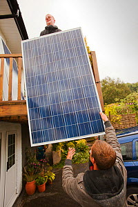 A technician fitting solar photo voltaic panels to a house roof in Ambleside, Cumbria, UK. August 2011 - Ashley Cooper