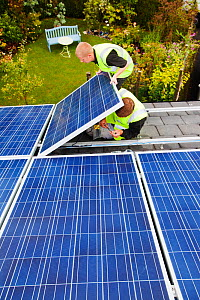 Technicians fitting solar photo voltaic panels to a house roof in Ambleside, Cumbria, UK. August 2011 - Ashley Cooper