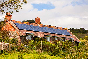 Solar panels on an old house on the Dorset coast near Charmouth, UK. June 2012 - Ashley Cooper
