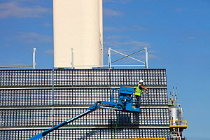 A man cleans high concentration photo voltaic panels being trialled by the research and development arm of Abengoa Solar, at their Solucar solar complex in Sanlucar la Mayor, Spain. Abengoa are invest... - Ashley Cooper