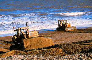 Bulldozers rebuilding the storm beach in Cley, Norfolk, England, UK. - Ashley Cooper