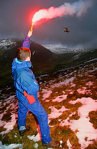 A mountain rescue member uses a flare to attract an approaching sea king helicopter to the casualty site on Fairfield, Lake District, England, UK. - Ashley Cooper