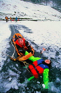 Members of the Langdale Ambleside Mountain Rescue Team rescue a man fallen through ice on Rydal Water, Lake District, England, UK. - Ashley Cooper