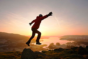 Man leaping at sunrise,  Lake Windermere from Todd Crag above Ambleside, Lake District, England, UK. January 2012 - Ashley Cooper