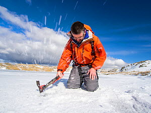 Mountaineer testing the thickness of ice on sprinkling Tarn to see if it safe to walk on, Lake District, England, UK. March 2013 - Ashley Cooper