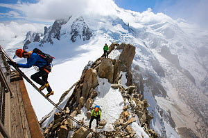 Mont Blanc from the Aiguille Du Midi above Chamonix, France, with climbers on the Cosmiques Arete, climbing the ladder to access the cable car station. September 2014 - Ashley Cooper