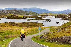 Woman cycling around the Golden road on the East side of the Isle of Harris, Outer Hebrides, Scotland, UK. June 2015 - Ashley Cooper
