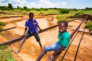 Children playing on tracks of railway bridge swept away by the January 2015 flooding leaving the tracks suspended in mid air, near Bangula. Malawi. March.  -  Ashley Cooper