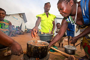 People displaced by flooding at  Chiteskesa refugee camp,  cooking on a fuel efficient stove.  near Mulanje, Malawi. March 2015. - Ashley Cooper