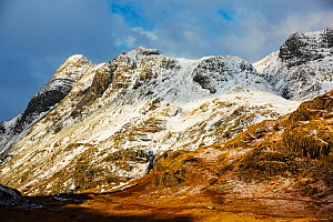 The Langdale Pikes from Blea Tarn. With a car driving over the Blea Tarn road into Little Langdale, Lake District, England, UK, January. - Ashley Cooper