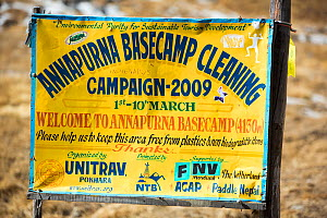 Annapurna base camp at 4130 metres in front of Annapurna South summit, , with a sign about a cleanup campaign. Annapurna Sanctuary, Himalayas, Nepal. December 2012. - Ashley Cooper