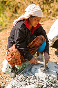 A Nepalese woman crushing stone with a hammer, Himalayan foothills, Nepal. January 2013. - Ashley Cooper