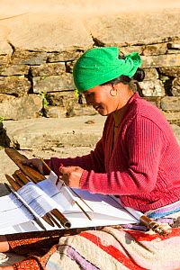 Nepalese woman in traditional clothing weaving cloth on a hand loom in the Himalayan foothills, Nepal. January 2013. - Ashley Cooper