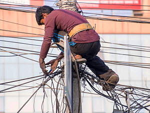 Electrician works on a tangle of electric wires in Kathmandu, Nepal. December 2012. - Ashley Cooper