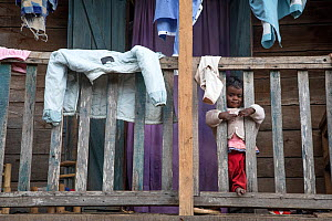 Child looking through balcony bars  in Andasibe village, Eastern Madagascar. August 2017.  -  David  Pattyn