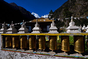 Prayer wheels and flags at the the local Buddhist  temple, Lower Yubeng village, Meili Snow Mountain , National park, Yunnan, China, October 2017. - Staffan Widstrand / Wild Wonders of China
