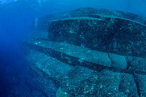 Scuba diver exploring the Yonaguni Monument, a submerged rock formation off the coast of Japan. It is unknown if these sandstone rocks are formed naturally or are of human construction, Yoguni, Japan.... - Stephane Granzotto