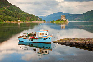 Boat in Loch Duich with Eilean Donan Castle in background, Highlands, Scotland, UK. July 2012.  -  Guy Edwardes