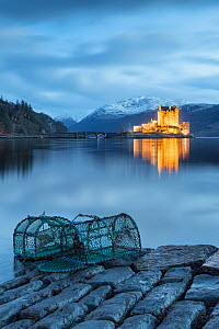 Lobster pots at edge of Loch Duich, Eilean Donan Castle in background. Highlands, Scotland, UK. January 2014. - Guy Edwardes