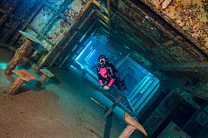 Diver swimming through wreck, mess hall of USS Kittiwake, US Military submarine rescue vessel. Seven Mile Beach, Grand Cayman, Cayman Islands, British West Indies. Caribbean Sea. January, 2018. - Alex Mustard