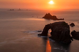 Sunset through Enys Dodnan Arch, with the Armed Knight rock and Longships lighthouse in the distance, Land's End, Cornwall, UK. May 2018.  -  Ross Hoddinott