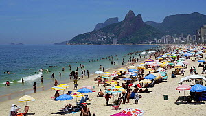 View of beachgoers on Ipanema Beach, with Dois Irmaos mountain in the background, Rio de Janeiro, Brazil, South AmericaSeptember 2016. (This image may be licensed either as rights managed or royalty f... - Gavin Hellier