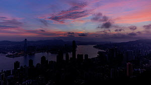 Timelapse of the sun rising over Hong Kong Central and Victoria Harbour, seen from Victoria Peak, Hong Kong, China, June 2017. (This image may be licensed either as rights managed or royalty free.)  -  Gavin Hellier