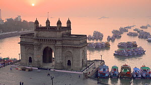 Static shot of the sun setting behind the Gateway of India, Mumbai, Maharashtra, India, January 2018. (This image may be licensed either as rights managed or royalty free.)  -  Gavin Hellier