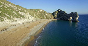 Aerial tracking shot along the shore towards Durdle Door, Dorset, England, UK, May 2017. (This image may be licensed either as rights managed or royalty free.) - Gavin Hellier