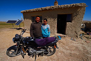 Mongolian shepherd Ge Ri Li Ao De and his wife Ao Te Gen with their motorbike in front of house with solar panels, Inner Mongolia, China. May 2016  -  Staffan Widstrand / Wild Wonders of China