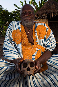 Local manon man in traditional robe with Chimpanzee (Pan troglodytes verus) skull,  Bossou, Republic of Guinea. December 2012. - Cyril Ruoso