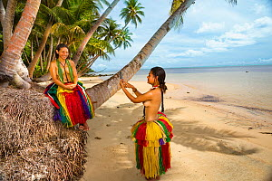 Two girls in traditional costume for cultural ceremonies taking a photo with a smartphone on beach. Yap, Micronesia. September 2013. Model released. - David Fleetham