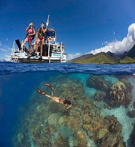 Two divers stepping off a dive boat into the Pacific Ocean with a snorkler in the reef below, split level view. Ukumehame, Maui, Hawaii. March 2014. Digital composite. Model released. - David Fleetham