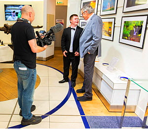 Photographers Oliver Hellowell and Ken Jenkins (Tennessee based photographer) being filmed at their joint exhibition at the T5 Gallery, Heathrow Airport, England, UK. July. - Oliver Hellowell
