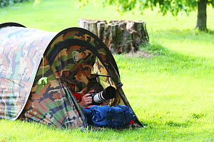 Photographer Oliver Hellowell taking pictures from a tent in the garden, England, UK. May 2015  -  Oliver Hellowell